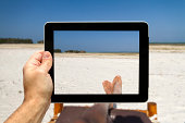 Man lying on beach chair Taking picture with digital tablet of a beach in Zanzibar