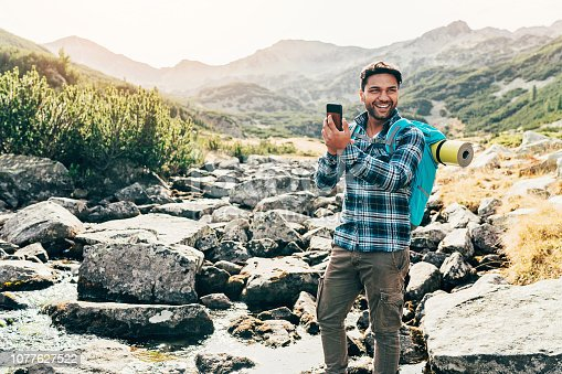 Smiling hiker taking picture with a smart phone high in the mountain
