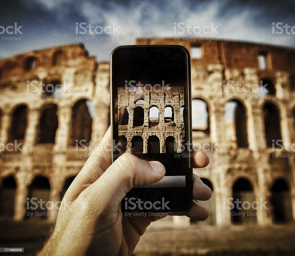 Taking pictures of the Coliseum with smartphone royalty-free stock photo