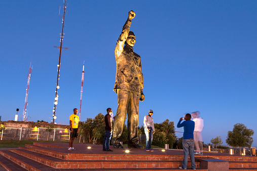 Bloemfontein, South Africa - November, 14th 2014: Teenagers posing for pictures with Nelson Mandela statue that overlooks down on Bloemfontein, situated on Naval Hill. Telecommunication aerials can be seen behind, on a sunset sky.