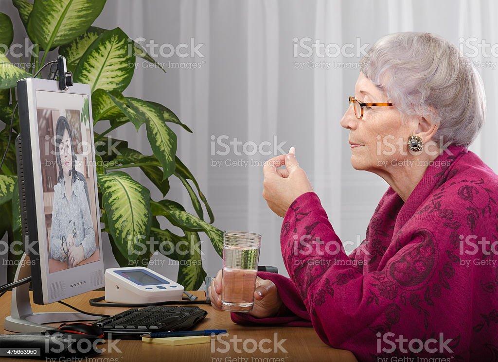 Taking pill during virtual doctor visit stock photo