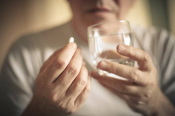 Taking pill. Senior man with pill. Focus is on hand. Close up. using mouth stock pictures, royalty-free photos & images