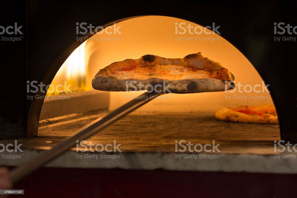 Taking Pizza out of Oven stock photo