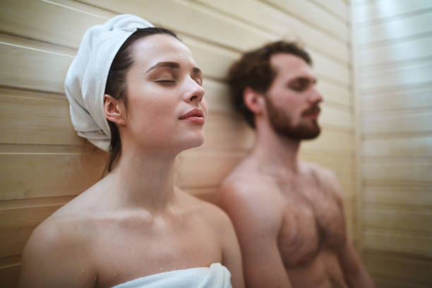 Taking pleasure Pleased woman enjoying time in sauna with her husband sauna stock pictures, royalty-free photos & images