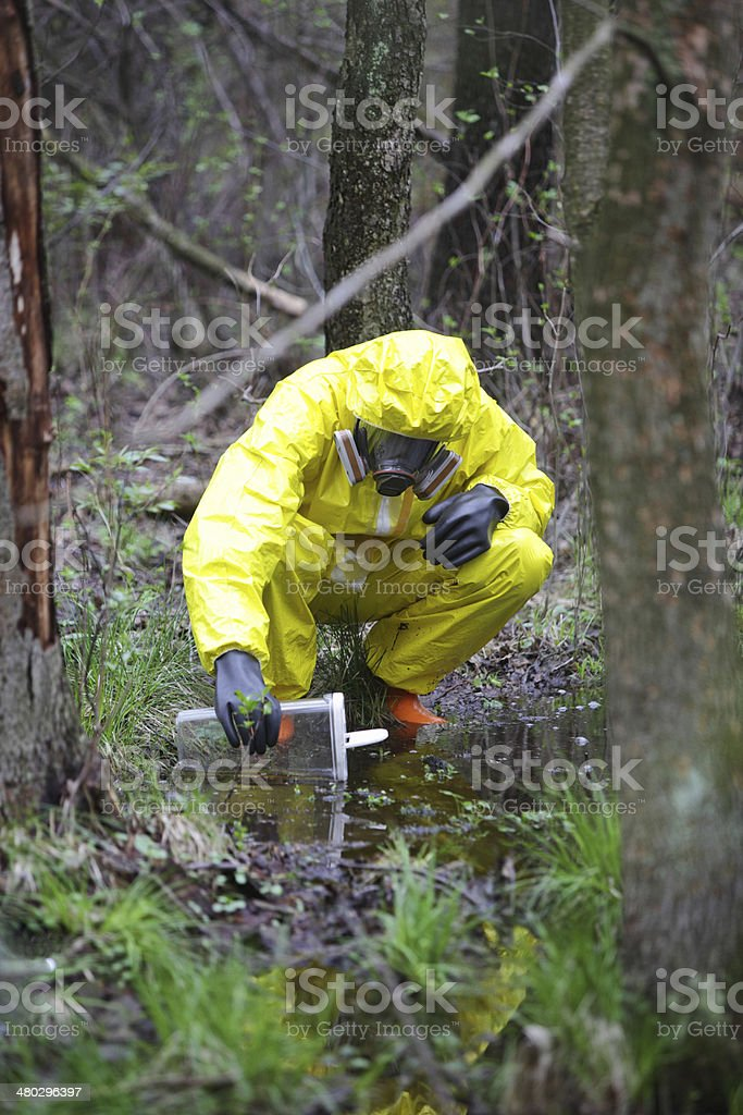 taking sample of water to container in floods contaminated area stock photo