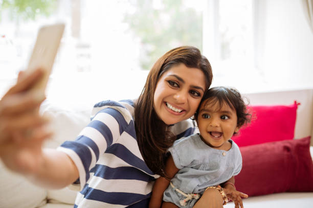 Taking selfie with child Smiling Indian young woman taking selfie with her little daughter indian family stock pictures, royalty-free photos & images