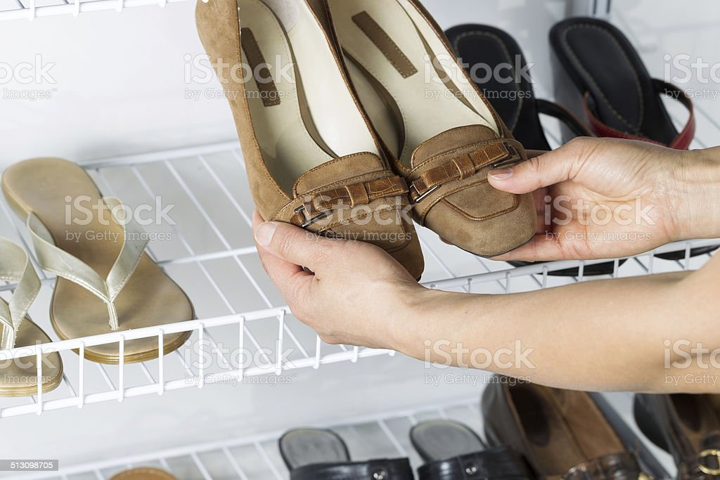 Taking shoes off wall mount rack in home stock photo