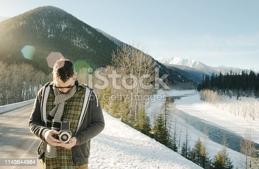 Shot of a young man holding a retro camera outdoors on a winter day
