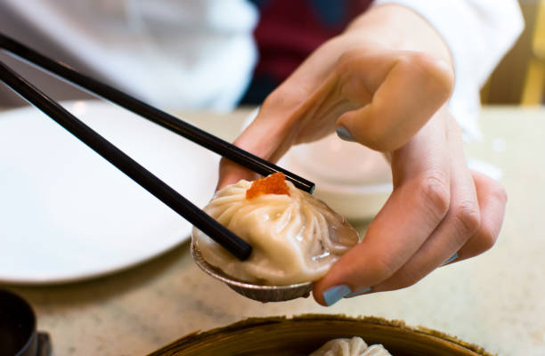 Taking steamed pork baozi in soup with chopsticks stock photo