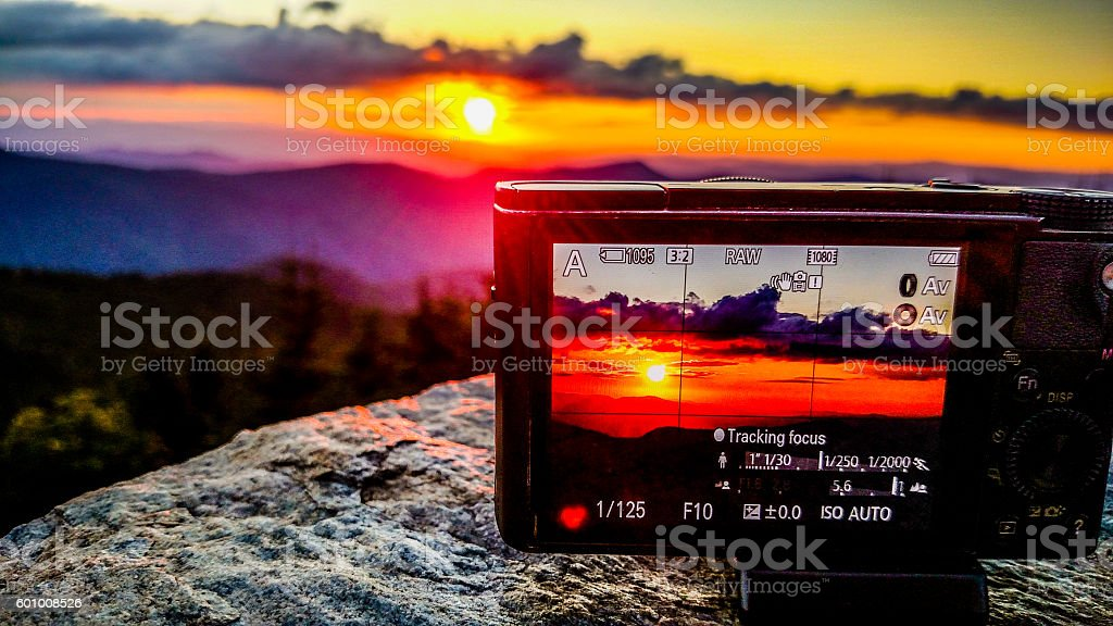 taking sunset photo with a camera in the mountains stock photo