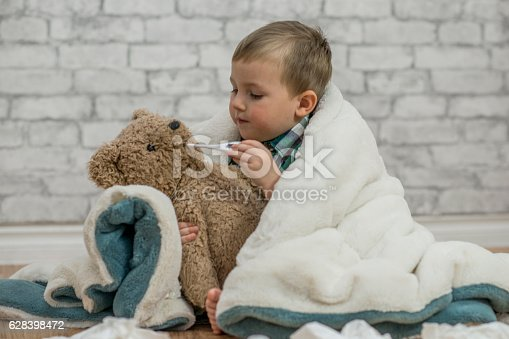 A young boy sits with his stuffed bear under a blanket. He is sick with the flu in flu season. Here he takes the teddy bear's temperature and cares for him while surrounded by facial tissues.