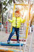 Little asian boy taking the challenge to cross a rope and wooden bridge obstacle.