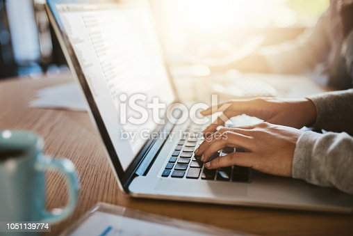 Closeup shot of an unrecognizable woman using a laptop with her husband in the background