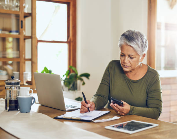 taking the day to sort her household budget - financial planning stock pictures, royalty-free photos & images