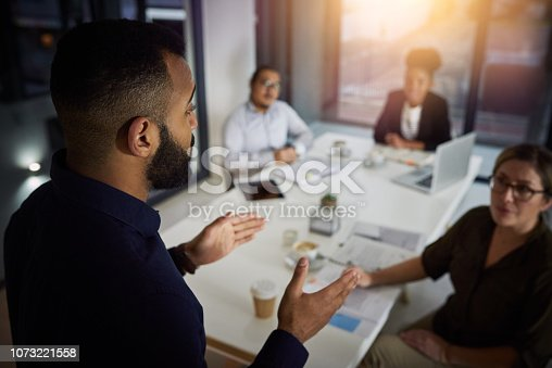 Shot of a young businessman delivering a presentation to his colleagues in the evening at work