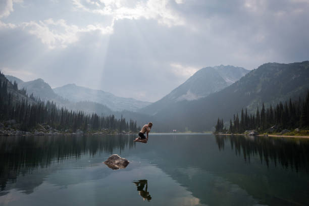 Taking the plunge Jumping into a lake in the mountains taking the plunge stock pictures, royalty-free photos & images