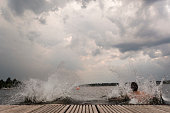 istock taking the plunge: young adults jump into Wannsee lake 1170462337
