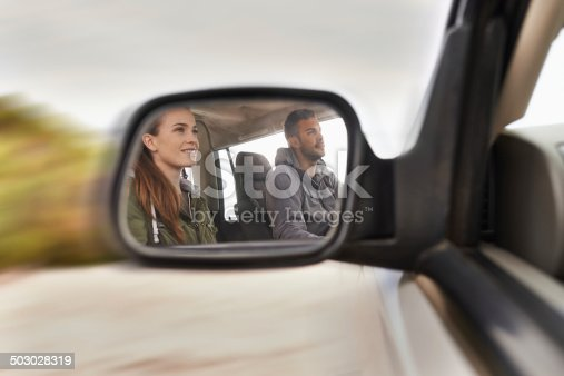 Cropped hot of a young couple on a road trip reflected in a car's side mirror