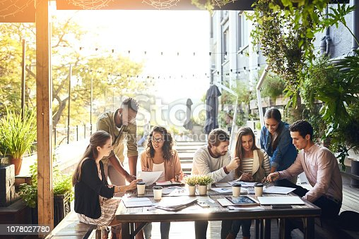 Cropped shot of a group of colleagues having a meeting outside at a cafe