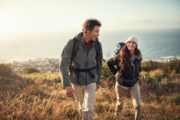 llevando su cita a la cima de la montaña - excursionismo fotografías e imágenes de stock