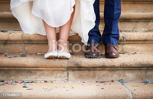 Cropped shot of a couple standing on steps after their wedding ceremony