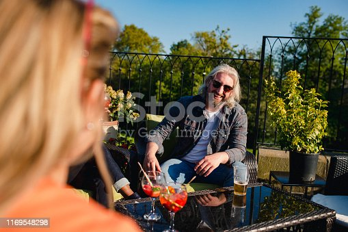 An over the shoulder view of a hipster man sitting outdoors in the sun enjoying a drink with friends.