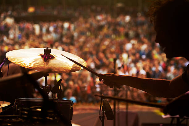 Taking to the stage Cropped shot of a drummer playing in front of a large crowd at an outdoor music festival drummer stock pictures, royalty-free photos & images