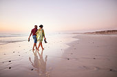 Shot of young couple walking together barefoot along the beach