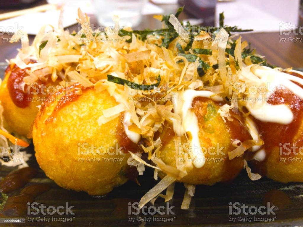 Takoyaki is a Japanese snack in the shape of little round balls containing pieces of octopus that wrap with flour, made from potatoes stock photo