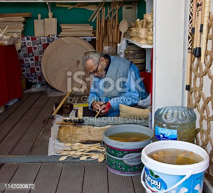 Istanbul, Turkey, February 17, 2019: There is a carpenter making wooden spoon at open air bazaar that seller exhibits hand craft in istiklal street, istanbul-turkey. Lots of people visit the mall on the street. Taksim is the region preferred by tourists at the same time. There are istiklal Avenue down the square that known in English as Independence Avenue, the most famous shopping street in the country sees as many as three million pedestrians on a busy weekend day.