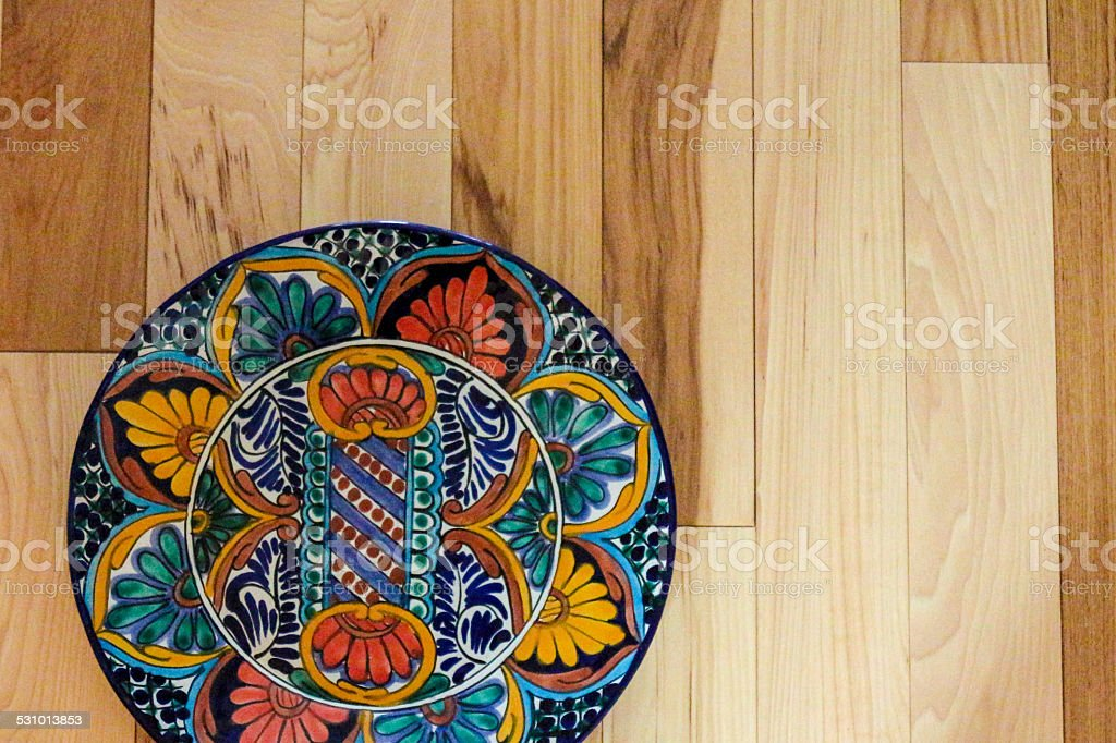 Talavera plate with a busy pattern on hickory stock photo