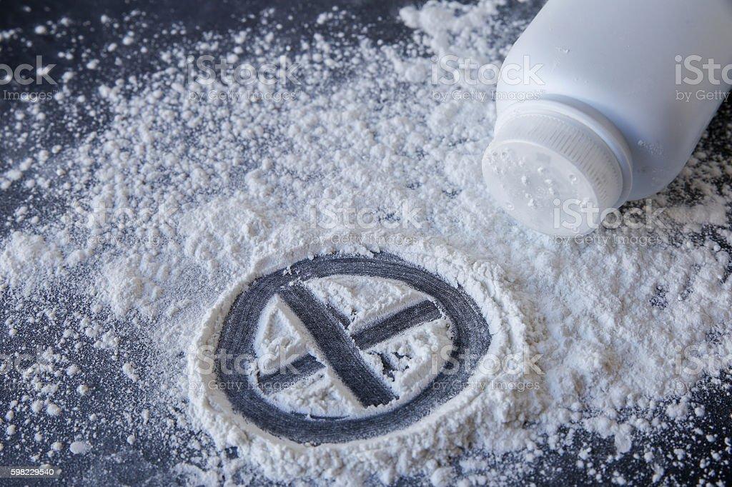 Talcum powder with cross sign on black background stock photo