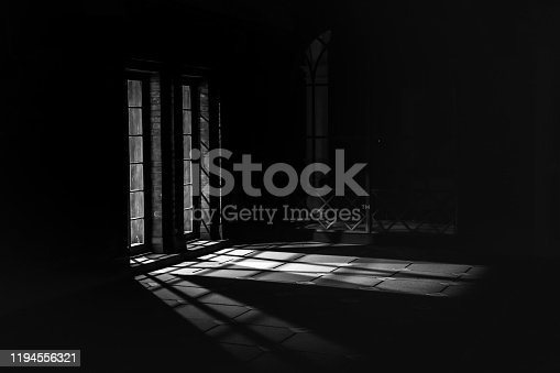 Black and white image of light coming out of a window into the darkness