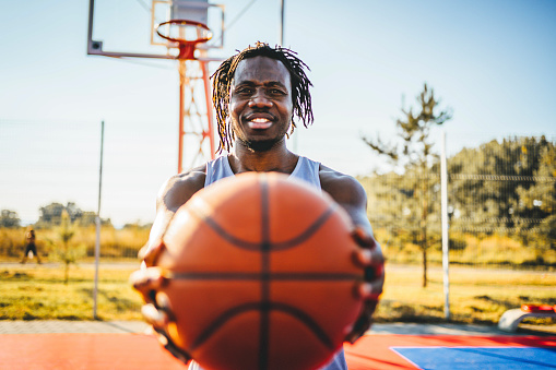 Smiling african male basketball player with a ball on the court