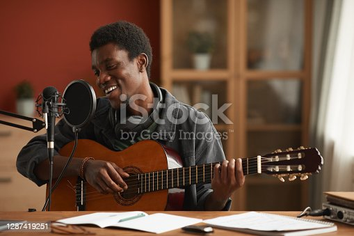 Portrait of talented African-American man singing to microphone and playing guitar while recording music in studio, copy space
