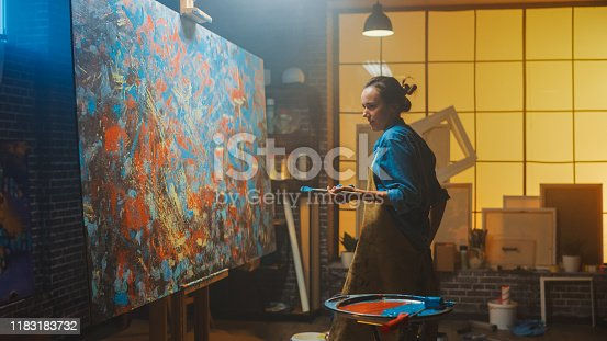 910798810 istock photo Talented Female Artist Drawing with Paint Brush Energetically and Enthusiastically, She Creates Modern Masterpiece of the Oil Painting. Creative Studio with Large Canvas. View Arc Shot 1183183732
