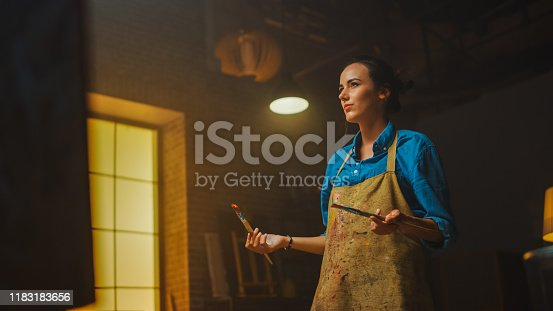 910798810 istock photo Talented Female Artist Drawing with Paint Brush Energetically, She Creates Modern Masterpiece of the Oil Painting. Creative Studio with Large Canvas of Striking Colors. Low Angle Portrait 1183183656