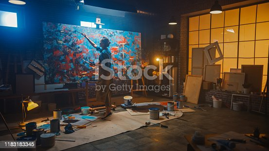 istock Talented Female Artist Working on a Modern Abstract Oil Painting, Gesturing with Broad Strokes Using Paint Brush. Dark Creative Studio Large Picture Stands on Easel Illuminated, Tools Everywhere 1183183345