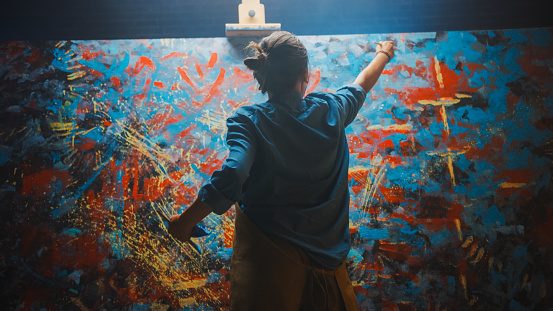 Talented Female Artist Works on Abstract Oil Painting, Using Paint Brush She Creates Modern Masterpiece. Dark and Messy Creative Studio where Large Canvas Stands on Easel Illuminated.