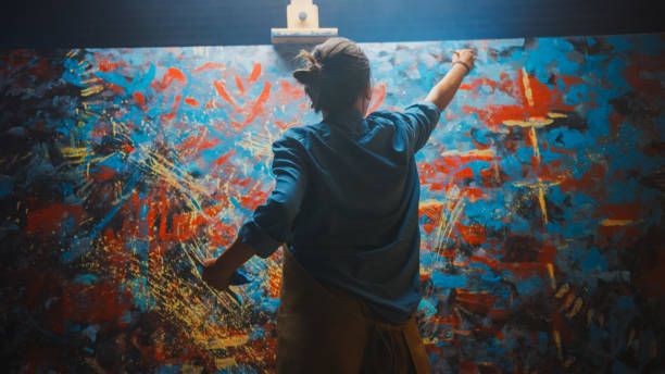 talented female artist works on abstract oil painting, using paint brush she creates modern masterpiece. dark and messy creative studio where large canvas stands on easel illuminated. - malarstwo zdjęcia i obrazy z banku zdjęć