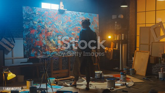 Talented Female Artist Works on Abstract Oil Painting, with Broad Strokes of Paint Brush She Creates Modern Masterpiece. Dark and Messy Creative Studio where Large Canvas Stands on Easel Illuminated