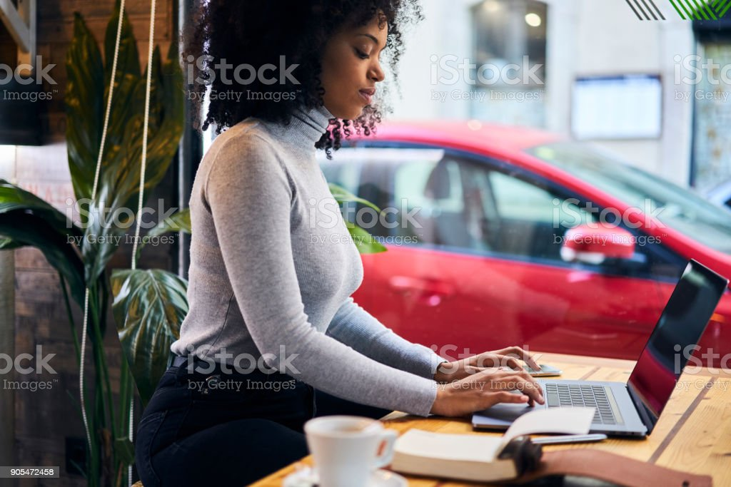 Talented female journalist blogger typing on keyboard text of her new article review working in cafe waiting for feedbacks from followers and colleagues using wireless connection to 4G internet stock photo