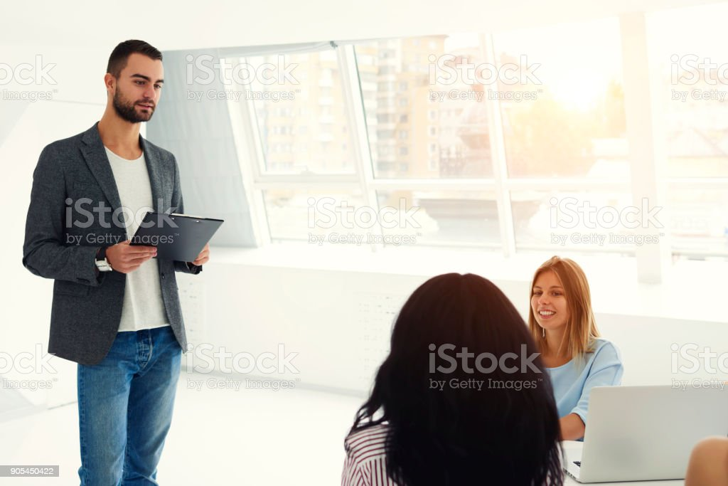 Talented male IT programmer making presentation of new software speaking about advantages and usability during briefing in coworking space of company speaking to crew of young professionals using wifi stock photo