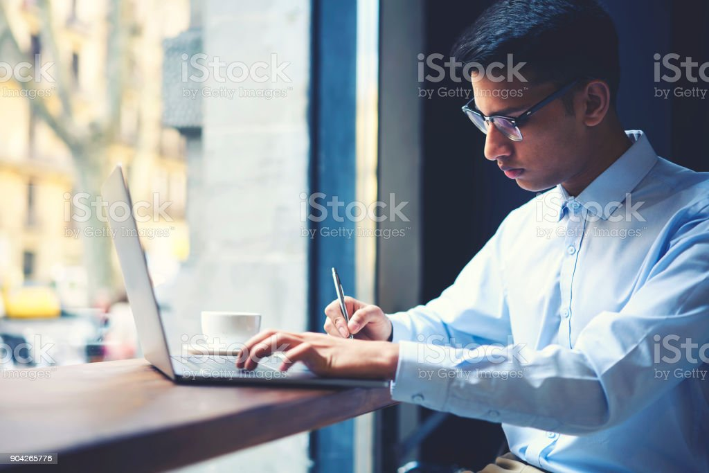 Talented male student of literature faculty of university making researchers for best annual book due to rating on internet users writing report in notebook while searching information via laptop stock photo