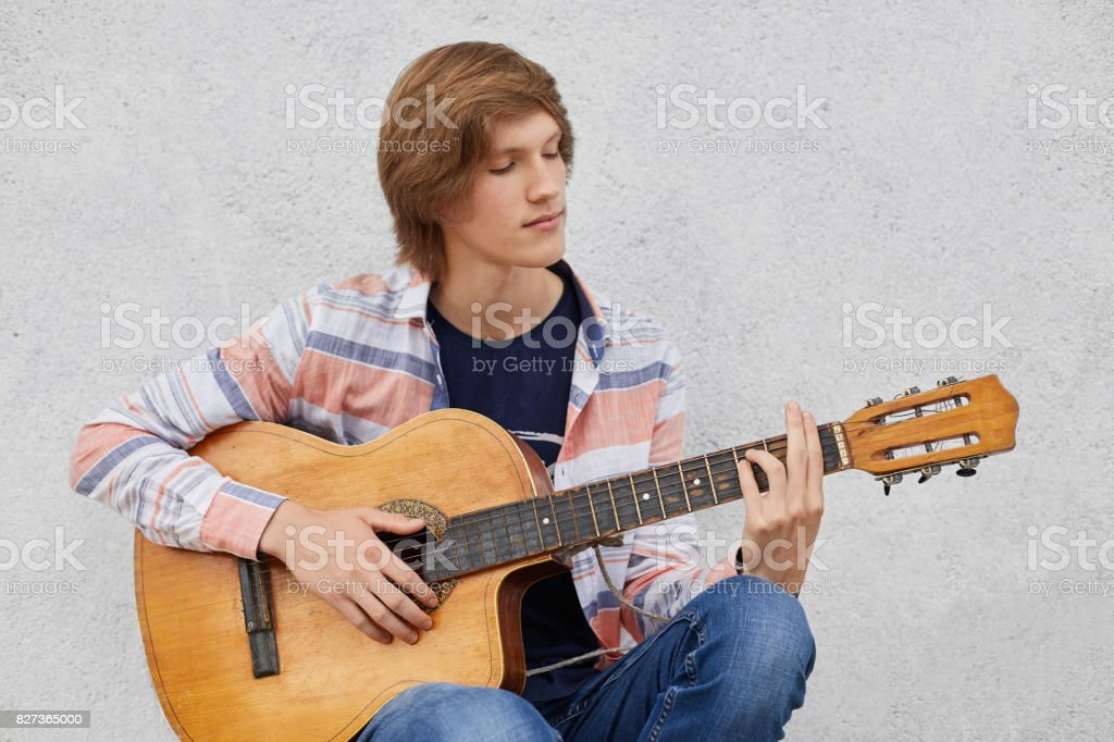 Talented Teenage Boy With Trendy Hairdo Wearing Shirt And Jeans Holding  Acoustic Guitar Playing His Favourite Songs While Sitting Against Grey