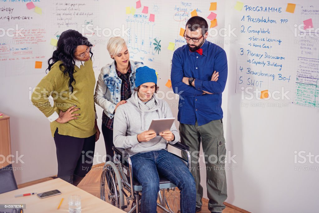 Talented young adults working together with disabled person in office stock photo