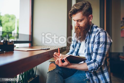 1174436608 istock photo Talented young bearded man in casual shirt drawing sketch in notebook enjoying leisure time in coffee shop.Skilled student writing down homework in notepad sitting in coworking.Copy space area 1159408370