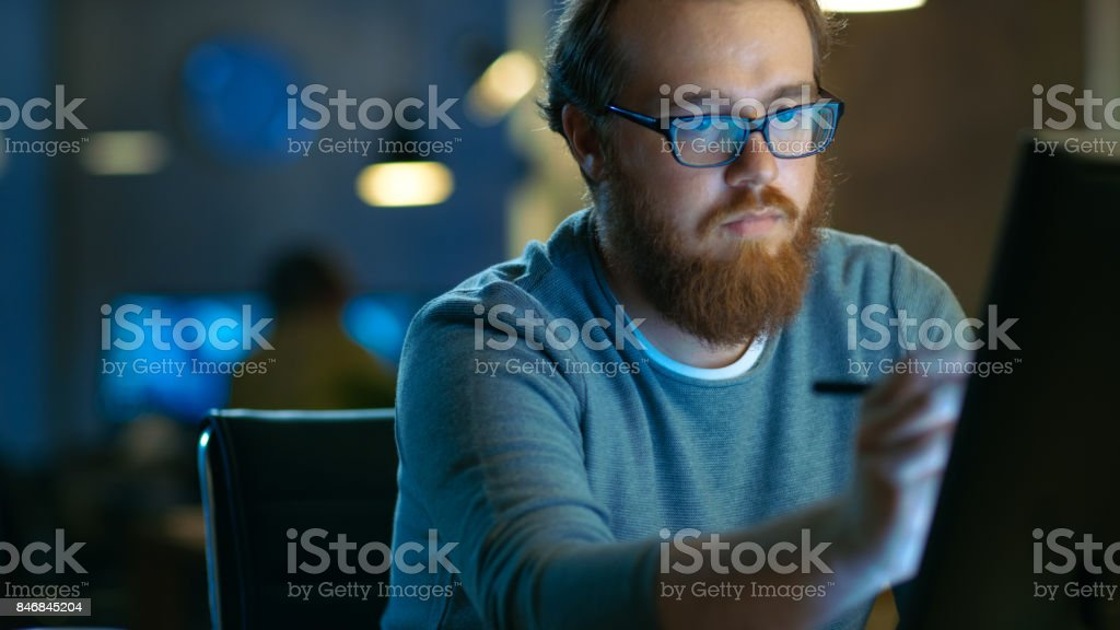 Talented Young Concept Artist Drawing on a Digital Pen Display Tablet While Sitting at His Working Place in Modern Loft Office. Late at Night. stock photo