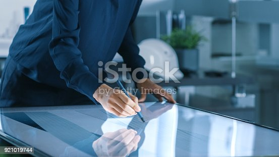 464482634istockphoto Talented Young Female Architectural Designer Draws Building Concept on a Graphics Tablet Display Vertical Touchscreen Table. Clean Minimalistic Office, Concrete Walls Covered by Blueprints. 921019744
