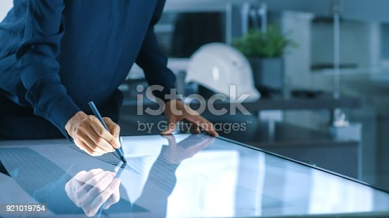 464482634istockphoto Talented Young Female Architectural Designer Draws Building Concept on a Graphics Tablet Display Vertical Touchscreen Table. Clean Minimalistic Office, Concrete Walls Covered by Blueprints. 921019754